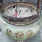 white pot with candle and ash in japan in photo by kathryn sassall